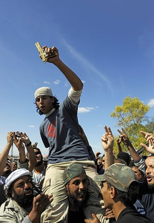 Libya celebrates: Young man holding the alleged gold-plated gun of Muammar Gaddafi