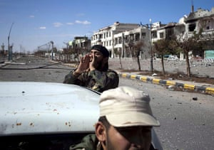 Libya celebrates: Libyan rebel fighters seen in a street  with destroyed buildings, in Sirte