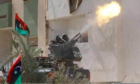 Anti-Gaddafi fighters fire in the air as they celebrate the death of Muammar Gaddafi