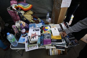 Occupy London: A man points at a book piled on a table