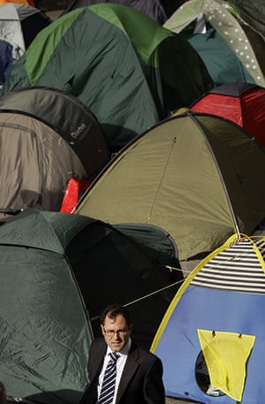 Occupy London: A commuter walks past tents put up by protesters
