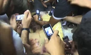 Muammar Gaddafi 'trophy' body on show in Misrata meat store