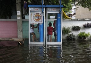 Thailand floods : Children play in flooded telephone booths in  Thung Song Hong , Bangkok