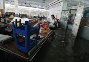 Thailand floods : A teacher moves school supplies after floodwaters at Rajinee Bon school,