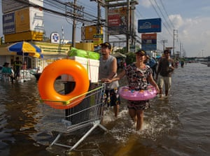 Thailand floods : Thai residents stock up on supplies walking down the flooded streets