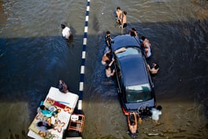 Thailand floods : Thai residents float a car  down a flooded street on  in Pathum Thani