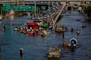 Thailand floods : Thai residents and traffic make their way through a flooded streets