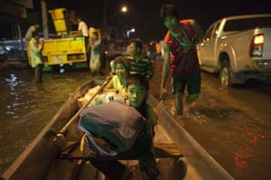Thailand floods : A family gets evacuated at night along the flooded streets of Bangbuathong