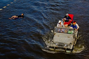 Thailand floods : Thai residents drive through flooded streets as a man floats downstream