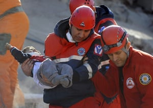earthquake in turkey: A rescue worker carries a boy to an ambulance