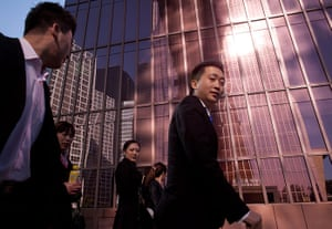 24 hours in pictures: Workers walk past an office building in Beijing, China