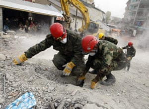 Turkey earthquake: An Azeri rescuer inspects a hole in the debris in Ercis