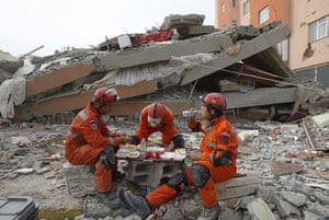 Turkey earthquake: Rescue workers rest near a collapsed building in Ercis
