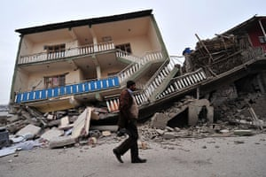 Turkey earthquake: A Turkish man walks past a collapsed building in Ercis