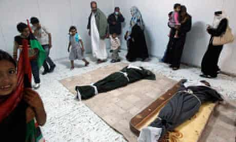 Libyans file past the bodies of Gaddafi and his son prior to their burial