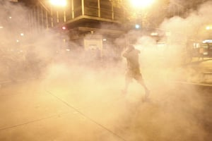 occupy oakland clashes: A masked demonstrator walks through a cloud of tear gas