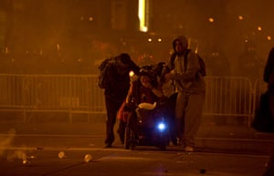 occupy oakland clashes: Activists help a wheelchair away from teargas