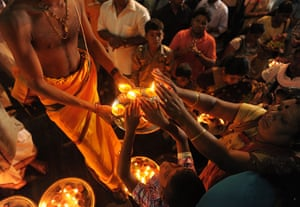 Diwali festival of lights: Sri Lankan Hindus receive blessings from a priest holding an oil lamp