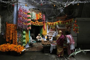 Diwali festival of lights: Indian women buy floral decorations and prayer material