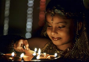 Diwali festival of lights: An Indian child lights earthen lamps on the eve of Diwali festival, Bhopal
