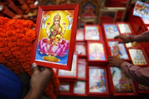 Diwali festival of lights: A Nepalese man selects a picture of Lakshmi