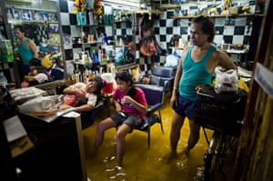 24 hours in pictures: Bangkok, Thailand: Residents watch television in a flooded beauty salon