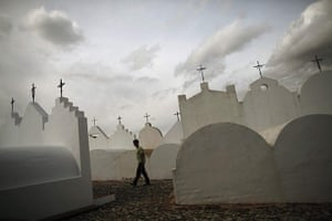 24 hours in pictures: Malaga, Spain: A man walks past tombstones at the cemetery of Casabermeja