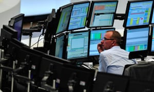 A trader sits in front of screens showing the German DAX index in Frankfurt