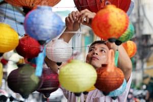 24 Hours: Hanoi, Vietnam: A man hangs lantern outside his shop