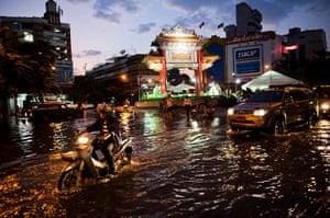 24 Hours: Bangkok, Thailand: Residents drive through a flooded street