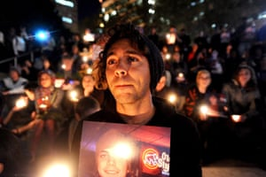 24 Hours: Oakland, US: Zachary Greer holds a photo of Scott Olsen during a vigil