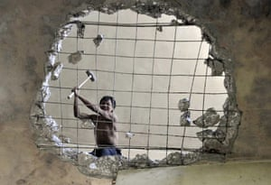 Guiyang urbanisation: A labourer demolishes a building to make way for a residential area