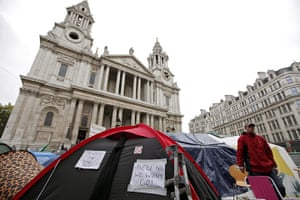 Occupy London protests: An Occupy London protester stands next to a tent with a pasted message