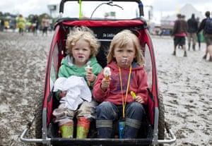 UK Festivals Exhibition: Tom and Matty eat ice cream at muddy Glastonbury, 2011