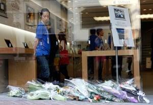 Steve Jobs Apple shrines: Tokyo, Japan: An employee looks at flowers at the Shibuya Apple store