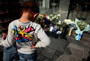 Steve Jobs Apple shrines: Beijing, China: A child looks at flowers laid in tribute to Steve Jobs