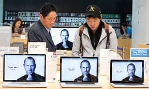 Steve Jobs Apple shrines: Seoul, South Korea: Customers look at products behind Apple computers