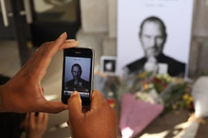 Steve Jobs tributes: London, UK: A man uses an iphone to photograph tributes to Steve Jobs