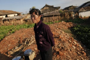 Famine in North Korea:  Jong Song Hui, a North Korean woman, stands in ruins of her home destroyed