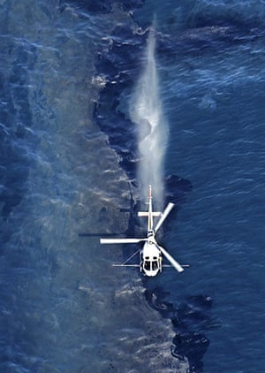 New Zealand oil spill: A helicopter sprays a dispersant on the oil slick