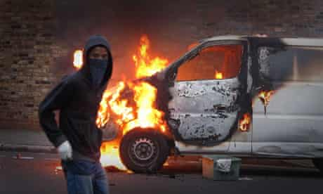 A hooded youth walks past a burning vehicle in Hackney, London, during the August riots