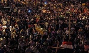 Egyptian Coptic Christians carry coffins during a mass funeral in Cairo