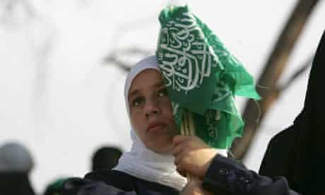 A Palestinian girl holds Hamas flags