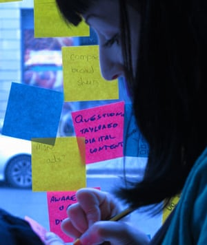 A student designer writing a Post-It note