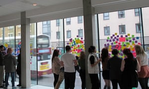 A group of student designers developing ideas using Post-It notes