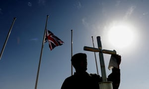 Armistice day: A soldier polishes the cross on a memorial at Camp Bastion in Afghanistan