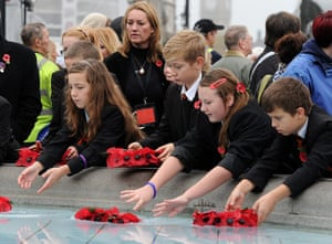 Armistice day update: Children place poppies in one of the fountains at Trafalgar Square