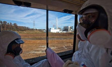 Men on board a bus going past the Fukushima Daiichi plant