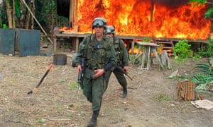 Counter-narcotics police officers destroy a cocaine laboratory in Colombia