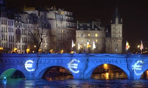 Blue lights reminiscent of the European flag and euro signs are projected on the Pont Neuf bridge